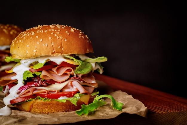 Домашний сэндвич с ветчиной из индейки с листьями салата, помидорами и сыром