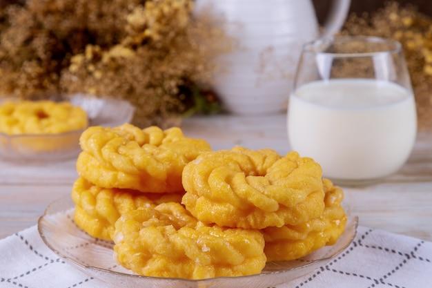 Французские пончики с глазурью и стакан молока на столе