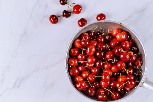 Ягодные вишни в миске дуршлаг с каплями воды на белой поверхности
