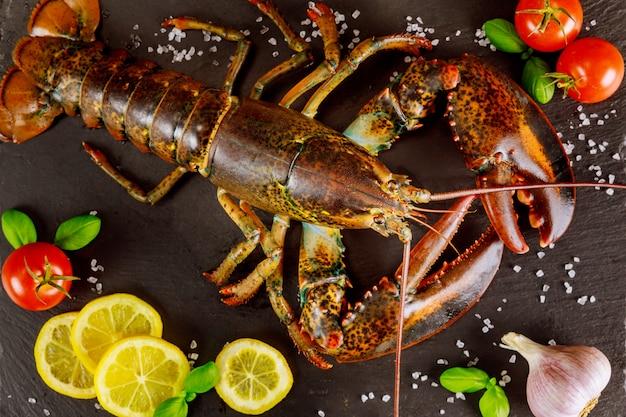 Свежий лобстер на черной доске со специями и овощами