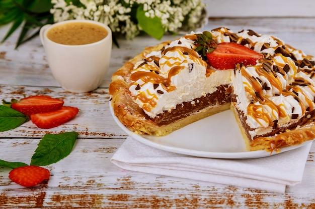 Нарезать карамельный пирог с чашкой кофе