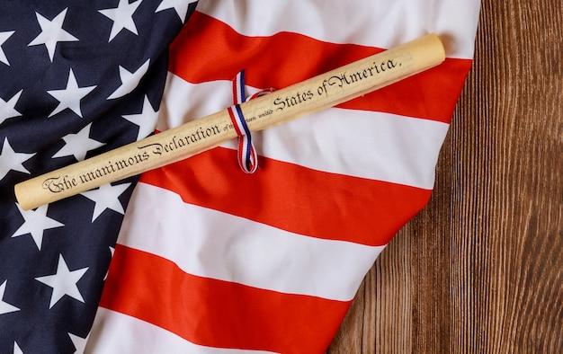 木製の背景に米国旗と羊皮紙ロールドキュメント