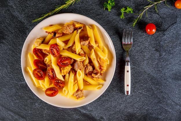 白いボウルに肉とチェリートマトのペンネパスタ