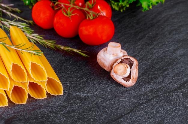 Сырые макароны из твердых сортов пшеницы со свежими помидорами и грибами