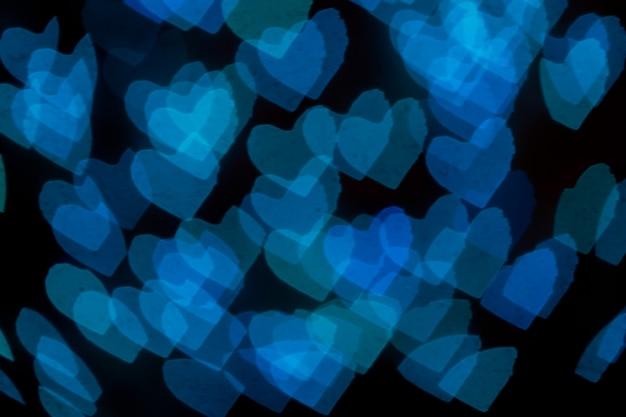 Размытые голубые сердца формирует боке на черном фоне