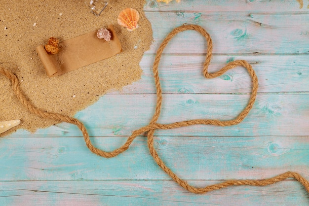 Сердце из веревки на берегу моря с ракушками