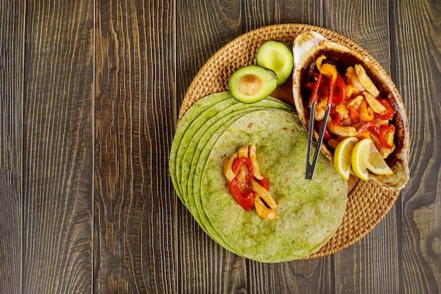 木製テーブルの上に炒めた牛肉と野菜のほうれん草ラップ