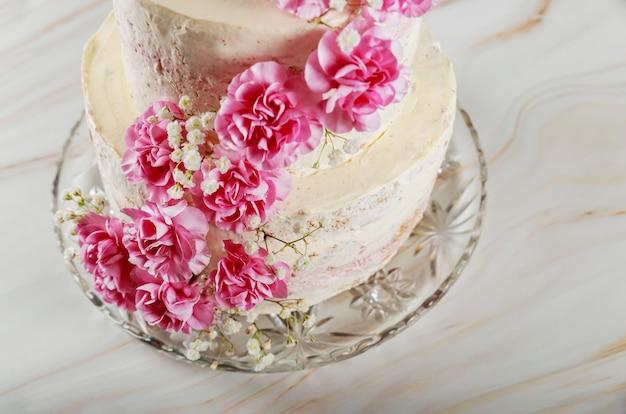 カーネーションの花と層状のウェディングクリームチーズケーキ