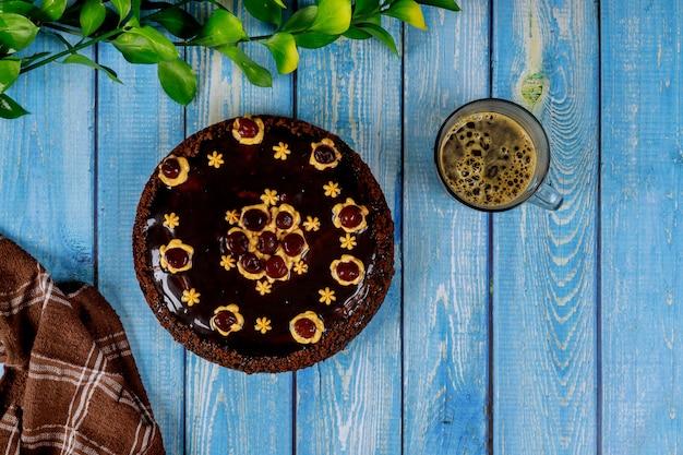 Шоколадный торт с вишней на вершине и чашкой кофе