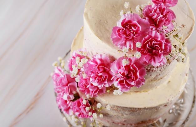 ピンクの花で飾られた結婚式の裸のケーキ