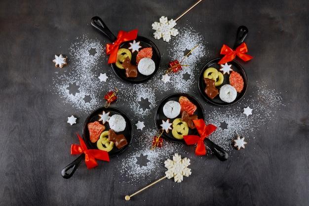Вид сверху сковороде рождественское печенье, шоколад и конфеты