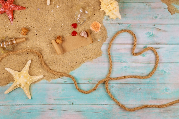 Сердце из морской веревки на берегу океана с ракушками и морскими звездами