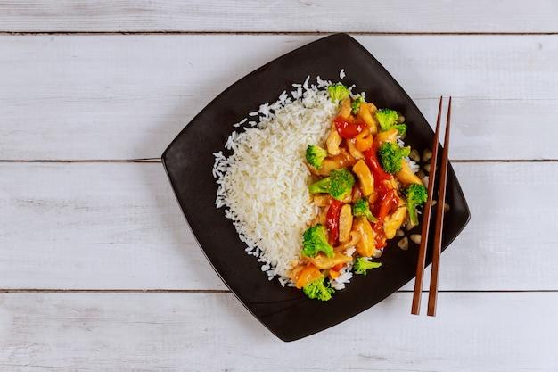 Рис с жареной курицей и овощами на черной квадратной тарелке китайская кухня.
