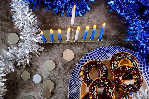 非常に熱い蝋燭、ドーナツ、チョコレートコインと本枝の燭台