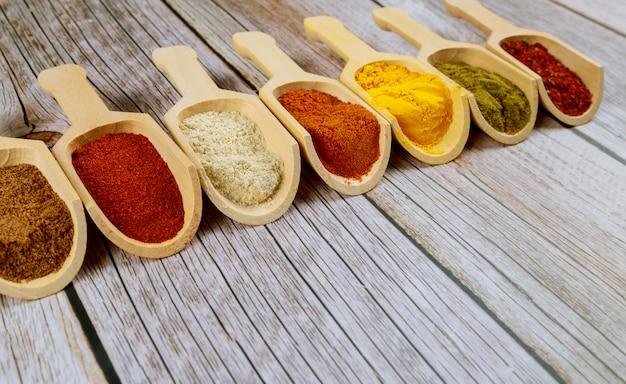 木製のテーブルに木製のスプーンで様々なスパイス