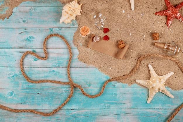 Сердце из веревки на берегу моря с ракушками, песком и морскими звездами