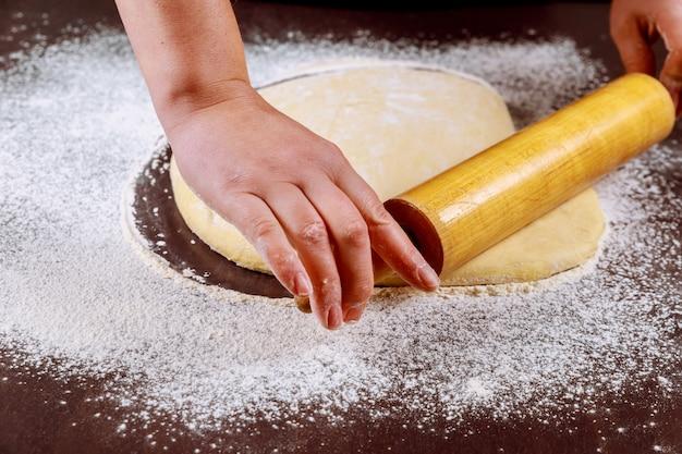 Женщина, раскатывающая тесто скалкой для изготовления булочек.