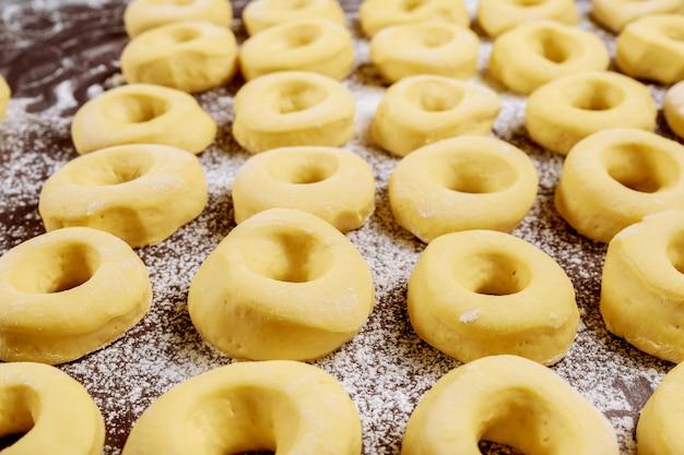 揚げる前に小麦粉でテーブルに生の丸いドーナツ