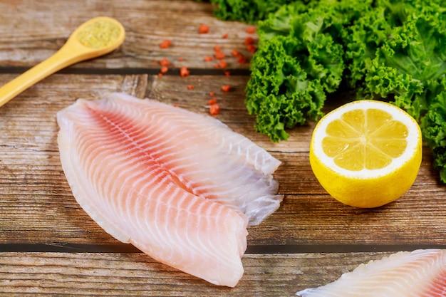 レモンと調味料の木製テーブルの上の新鮮な魚ティラピア