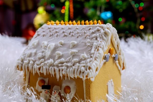 雪とクリスマスツリーの休日のジンジャーブレッドハウス