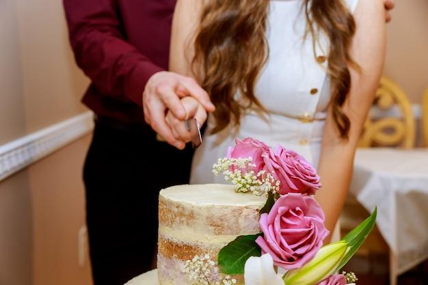 新郎新婦はピンクのバラでウェディングケーキを切っています。