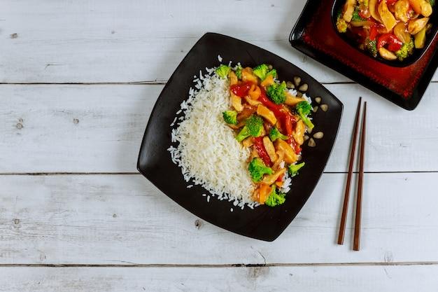 炒め鶏肉と野菜の黒い四角い皿にご飯。中華料理。