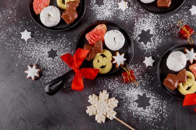Сковорода с вкусным рождественским печеньем и шоколадом на темной поверхности