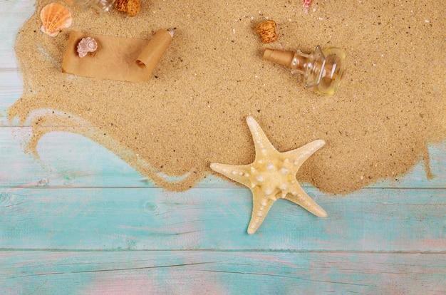 Морская звезда с ракушками на морской песок на синей деревянной поверхности