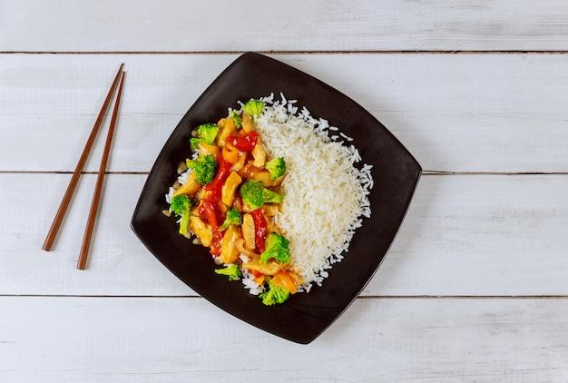 Рис с жареной курицей и овощами на черной квадратной тарелке