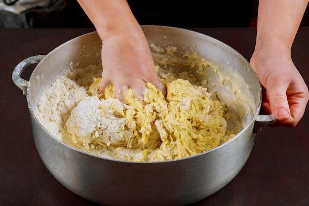 Женщина замешивает или смешивает дрожжевое тесто для приготовления булочек