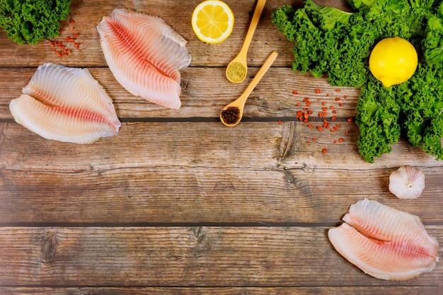素朴なテーブルに野菜と調味料と生ティラピアの切り身