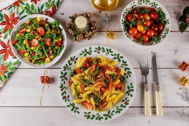 クリスマステーブルグリーンサラダとイチゴと色のパスタロティーニ。