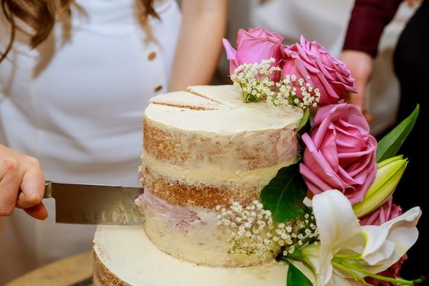 白いドレスの新郎と新婦は、新鮮な花で飾られたレイヤー裸のウェディングケーキをカット