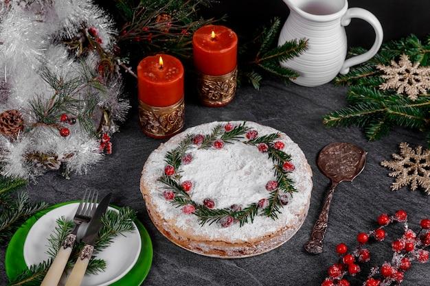 Праздничный праздничный пирог с клюквенным декором на черном столе с зажженными свечами