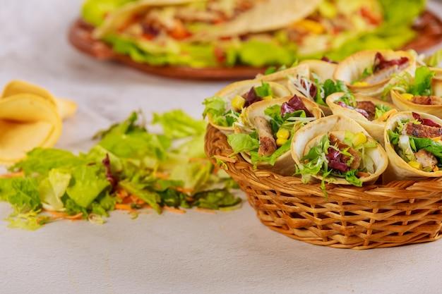 白いテーブルにグリーンサラダとバスケットに野菜と肉を詰めたトルティーヤコーン