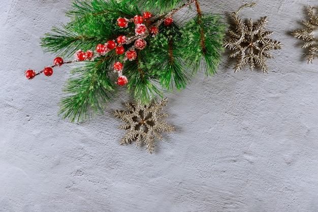 Рождественская поверхность с еловой веткой, красными ягодами и снежинками