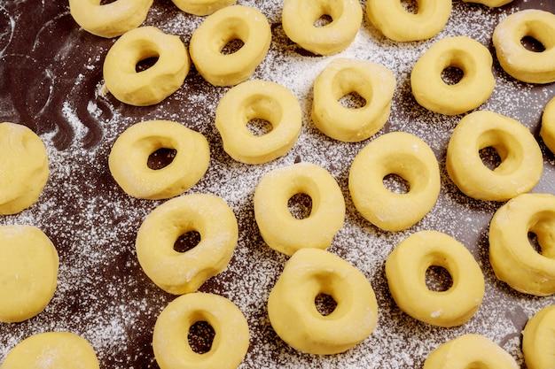 揚げる前に小麦粉でテーブルに調理されていない丸いドーナツ