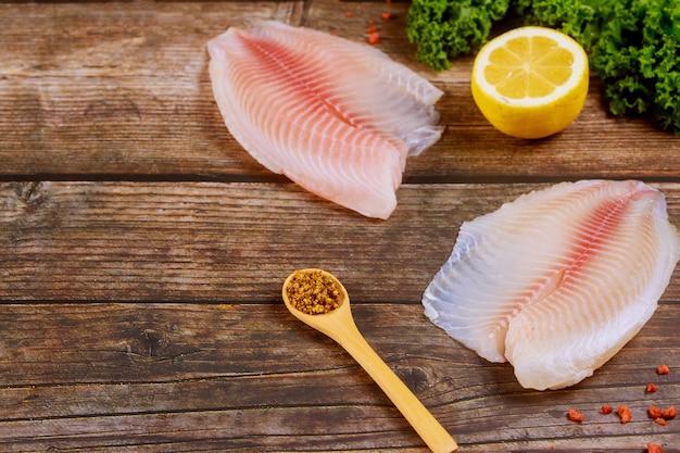 レモンと調味料のテーブルの上の有機魚ティラピア
