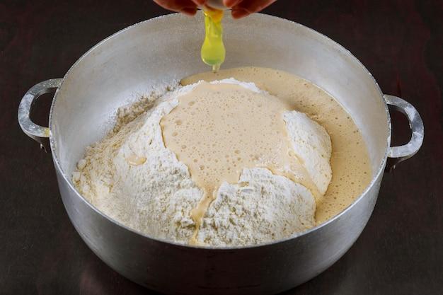 Добавляем яйцо в дрожжевое тесто для приготовления булочек