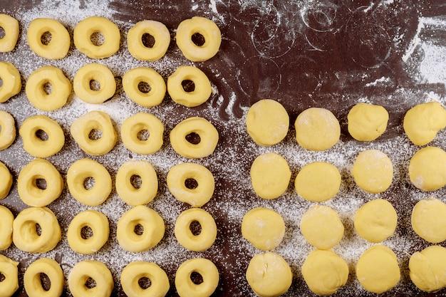 揚げる前に小麦粉でテーブルに調理されていない丸いドーナツとマンチカン