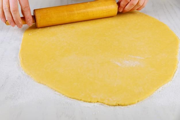 Женщина раскатывает тесто с булавкой для приготовления печенья на белом столе
