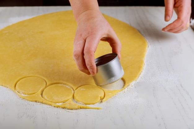 Женщина режет тесто для выпечки печенья на столе