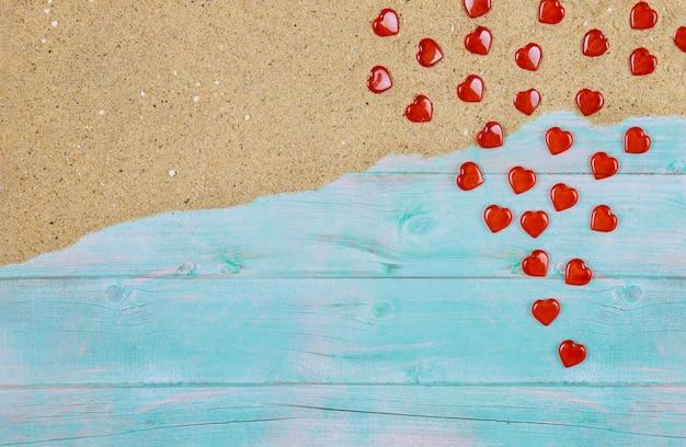 青い木製の背景の海砂の上の赤の公聴会。