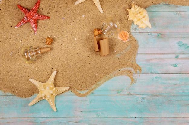 青い木製の背景の海砂の上の貝殻を持つヒトデ。コルクのガラス瓶からパピルス。