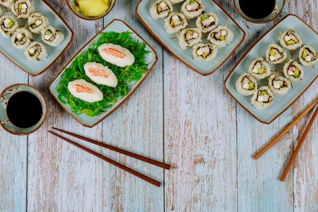 Китайская кухня. набор суши ролл с соевым соусом, имбирем и палочками.