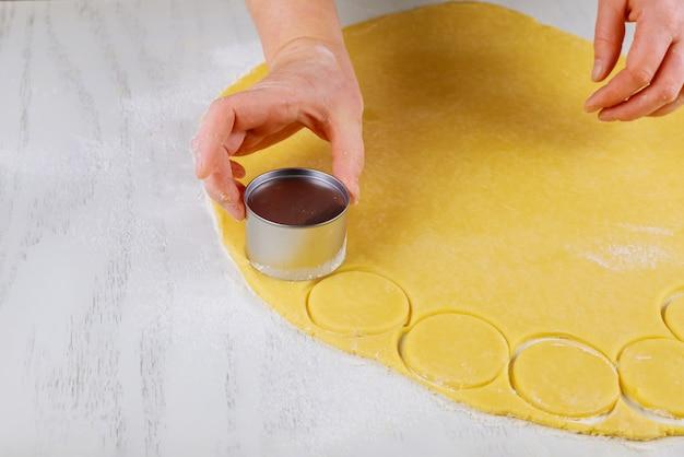 Женщина режет свернутое тесто для выпечки печенья на столе.
