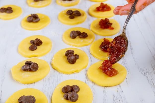 Заполнение варенья в сырые кружочки теста для печенья.