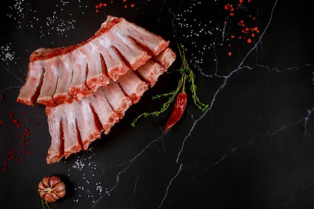 Сырые свиные ребрышки с травами, чесноком и перцем на черном фоне.
