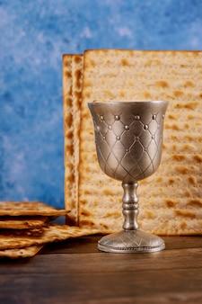 キッドゥッシュシルバーカップのワインとマッツォのパン。ユダヤ人のペサの休日。