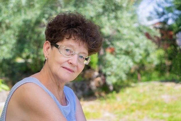 眼鏡をかけた年配の女性が自然の中に座って、カメラを見ています。老後、知恵と喜びのコンセプト。